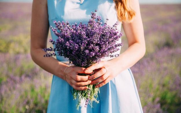 Blumenstrauß aus lavendel in den händen eines mädchens in einem blauen kleid Premium Fotos