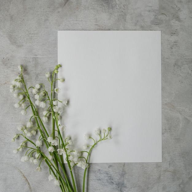 Blumenstrauß aus maiglöckchen auf grauem hintergrund mit einem leeren blatt weißes papier. Premium Fotos