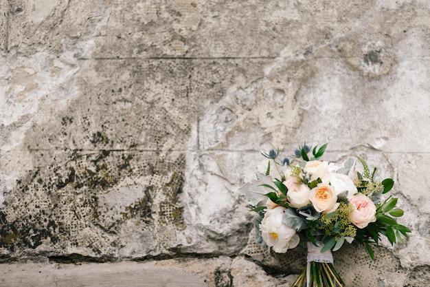 Blumenstrauß aus rosa und weißen poenies liegt vor einer betonmauer Kostenlose Fotos