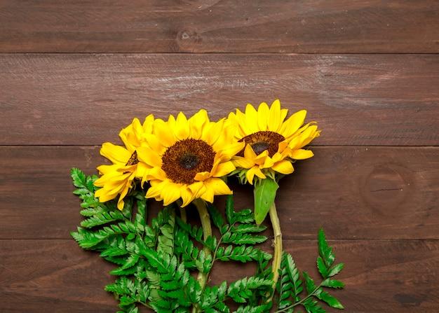 Blumenstrauß aus sonnenblumen und farnblättern Kostenlose Fotos