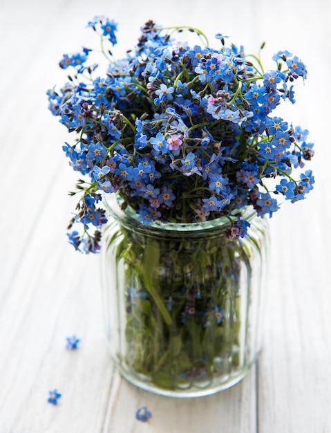 Blumenstrauß aus vergissmeinnicht in glasvase Premium Fotos