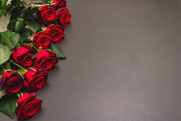 Blumenstrauß der frischen burgunderrosen auf einem schwarzen steinbetonhintergrund. duftende rote blumen, geschenkkonzept für valentinstag, hochzeit oder geburtstag Premium Fotos