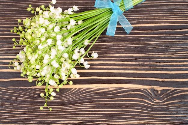 Blumenstrauß der maiglöckchen auf dem braunen hölzernen hintergrund. flache lage, draufsicht mit platz für text. Premium Fotos