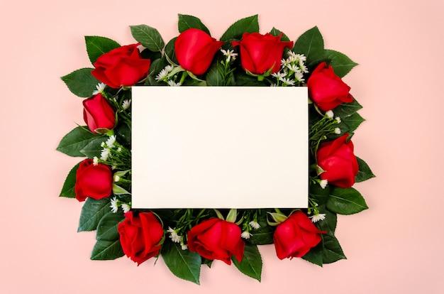 Blumenstrauß der roten rosen mit leerer weißbuchkarte. Premium Fotos