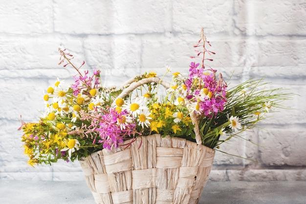 Blumenstrauß der schönen wildblumen in einem korb auf einem grauen hintergrund mit kopienraum. Premium Fotos