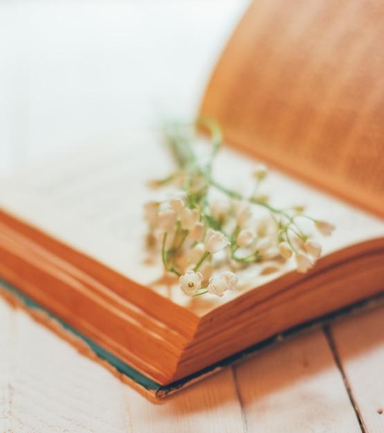 Blumenstrauß des maiglöckchens blüht auf einem offenen alten buch auf einer weißen weinlesetabelle, flache schärfentiefe Premium Fotos