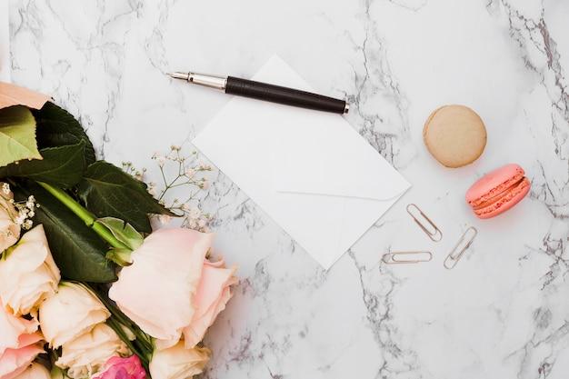 Blumenstrauß; füller; briefumschlag; büroklammer und makronen auf strukturiertem hintergrund des marmors Kostenlose Fotos