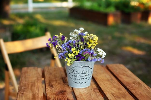 Blumenstrauß in der weinlesevase auf holztisch im garten Premium Fotos