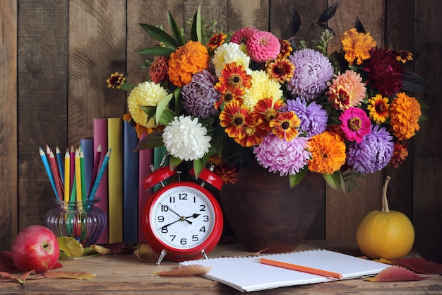 Blumenstrauß, kürbise, bleistifte, apfel, bücher und uhr auf dem tisch. stillleben. zurück zur schule. lehrertag. 1. september. Premium Fotos