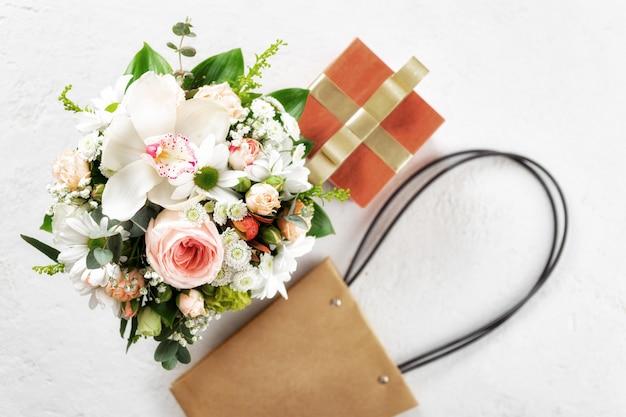 Blumenstrauß mit geschenkbox und tasche auf weißem hintergrund flache lage, blumenansicht zum valentinstag oder zum muttertagskonzept von oben Premium Fotos