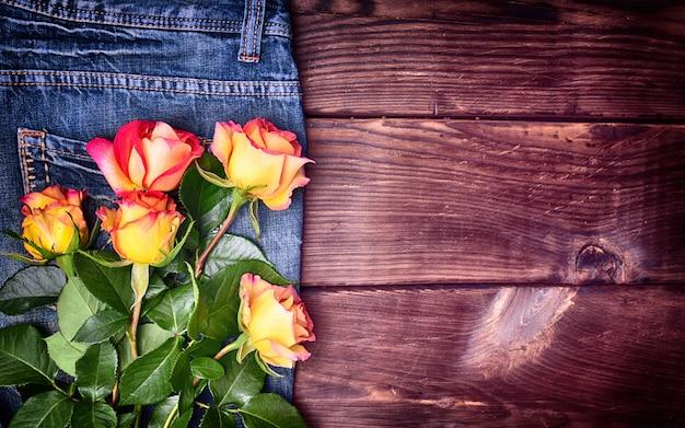 Blumenstrauß von blühenden rosen auf blue pants jeans Premium Fotos