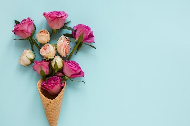 Blumenstrauß von den rosen eingewickelt in der eistüte mit kopienraumhintergrund Kostenlose Fotos