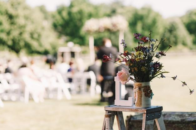 Blumenstrauß von feldblumen steht auf dem kleinen stuhl Kostenlose Fotos