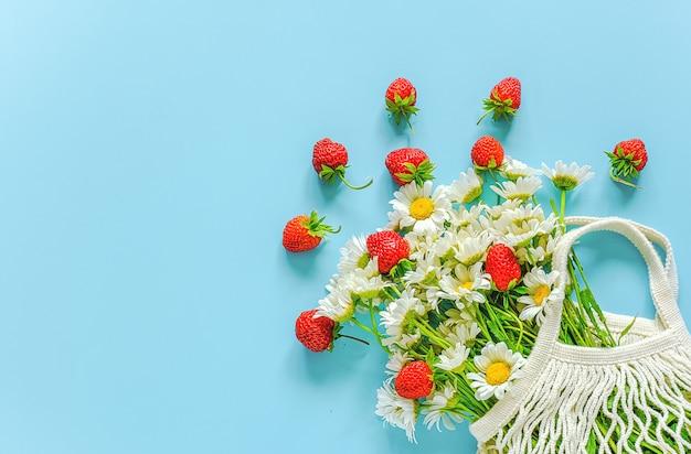 Blumenstrauß von feldgänseblümchen in wiederverwendbarer einkaufs-eco maschentasche und in den roten erdbeeren auf blauem hintergrund Premium Fotos