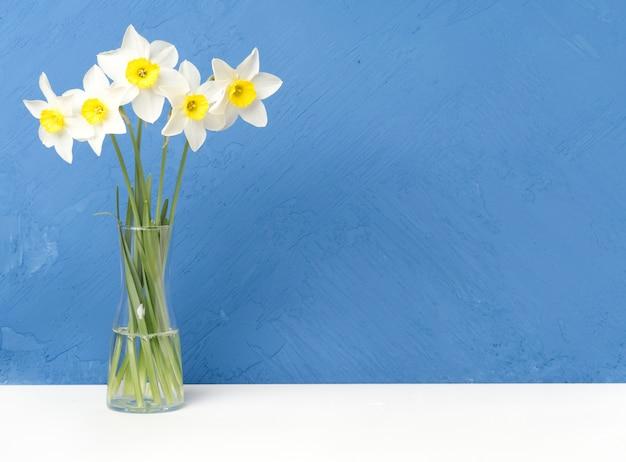 Blumenstrauß von frischen blumen, narzissen mit glasvase auf weißer tabelle, blaue wand Premium Fotos