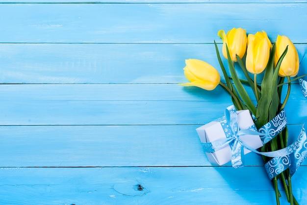 Blumenstrauß von gelben tulpen und von geschenk mit einem blauen band auf einem blauen hölzernen hintergrund Premium Fotos