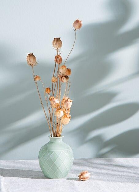 Blumenstrauß von getrockneten blumenmohnblumen in einer grünen vase auf einer leinentischdecke und morgenschatten auf pastellgrünem hintergrund. vorderansicht und kopierraum Premium Fotos