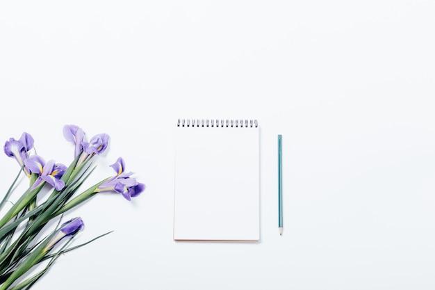 Blumenstrauß von iris und von notizbuch mit bleistift auf einer weißen tabelle Premium Fotos