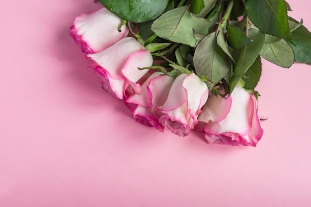 Blumenstrauß von rosa blühenden rosen auf pastellrosa Premium Fotos