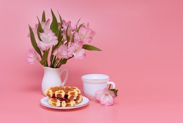 Blumenstrauß von rosa blumen auf einem rosa hintergrund. eine tasse kaffee mit milch und hausgemachten waffeln. Premium Fotos