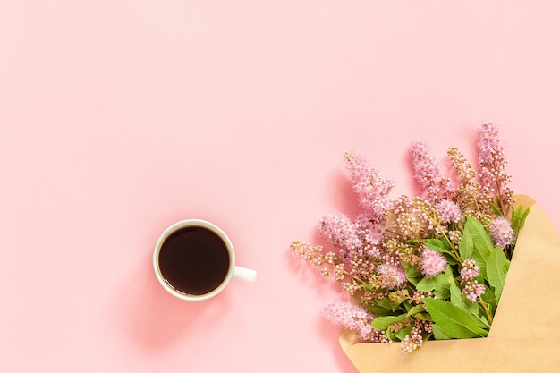 Blumenstrauß von rosa blumen im umschlag, im tasse kaffee und in einer weißen leeren karte für text auf rosa hintergrund Premium Fotos