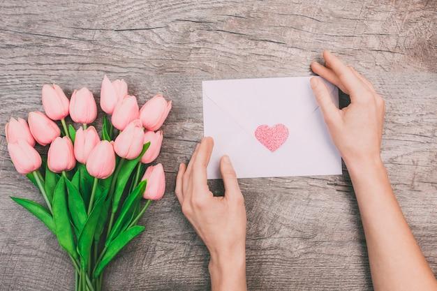 Blumenstrauß von rosa tulpen und frauenhänden halten einen leeren umschlag mit einem herzen, auf einem hölzernen hintergrund. Premium Fotos