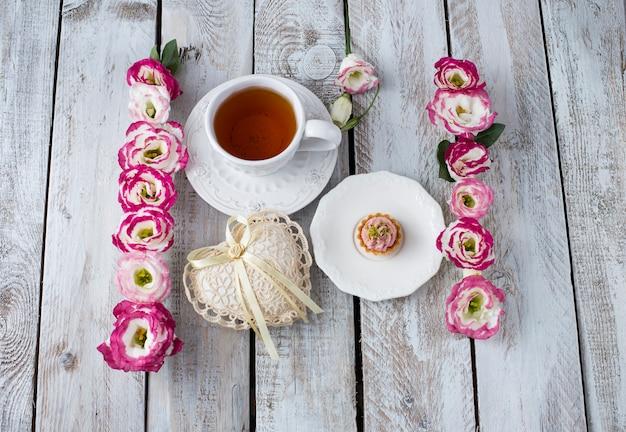 Blumenstrauß von schönen blumen mit tasse tee und herz aus spitze. feiertage hintergrund: 8. märz, valentinstag, muttertag, hochzeit, verlobung Premium Fotos