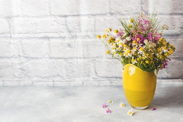 Blumenstrauß von schönen wildflowers im vase auf einer grauen oberfläche mit kopienraum. Premium Fotos