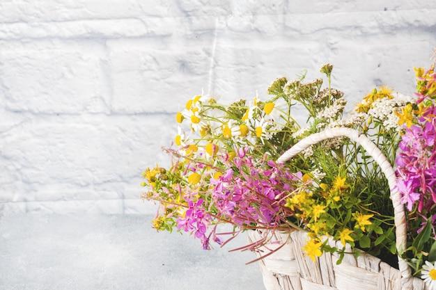 Blumenstrauß von schönen wildflowers in einem korb auf einer grauen oberfläche mit kopienraum. Premium Fotos