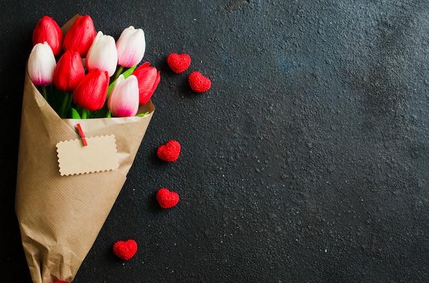 Blumenstrauß von tulpen und von geschenkbox auf dunklem hintergrund. Premium Fotos