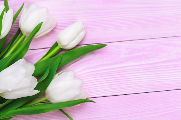 Blumenstrauß von tulpenblumen auf rosa hölzernem hintergrund mit kopienraum Premium Fotos