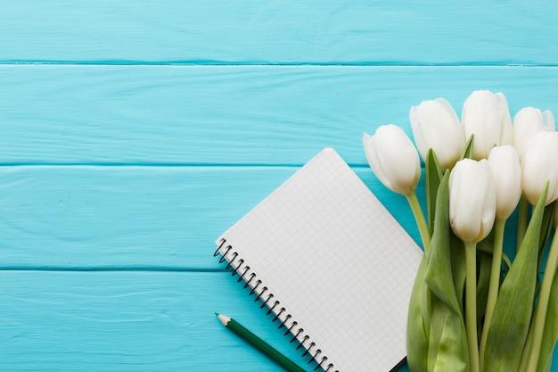 Blumenstrauß von tulpenblumen und von draufsicht des notizblockes Kostenlose Fotos