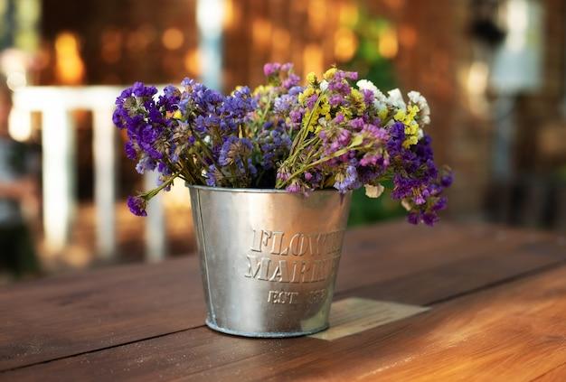 Blumenstraußblumen in der weinlesevase auf holztisch im garten. gemütliche einrichtung des innenhofs Premium Fotos