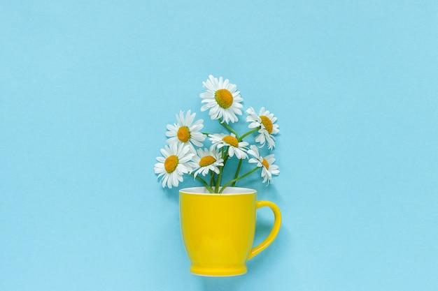 Blumenstraußkamillengänseblümchen blüht im gelben becher auf blauem pastellfarbpapierhintergrund Premium Fotos