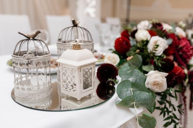 Blumenzusammensetzung mit eukalyptus-, weiß- und bordeauxrosen auf dem tisch und metallkäfigen auf einem spiegelbehälter Kostenlose Fotos