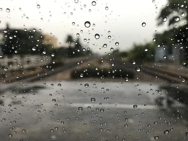 Blured hintergrund mit regen fällt auf glas und autos auf der eisenbahn Premium Fotos