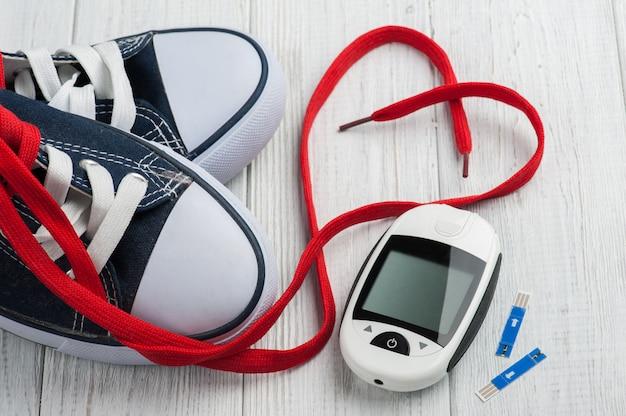 Blutzuckermessgerät, gummischuhe, rotes herz Premium Fotos