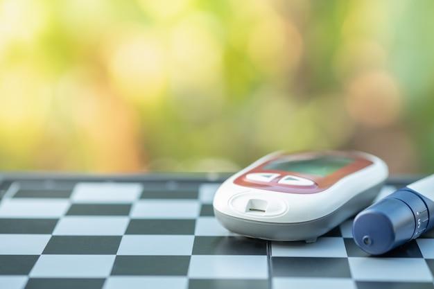 Blutzuckermessgerät und lanzette zur kontrolle des blutzuckerspiegels auf dem schachbrett. Premium Fotos