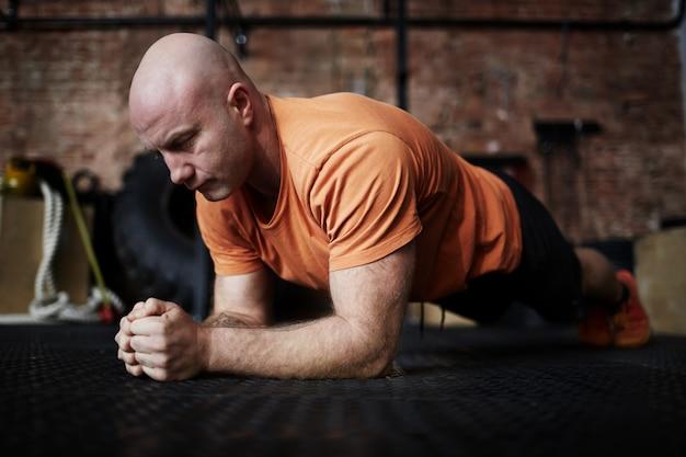 Bodybuilder, der in der planke steht Kostenlose Fotos