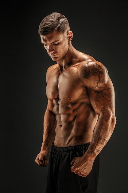 Bodybuilder, der mann mit muskeln der eignung auf dunkler szene aufwirft Premium Fotos
