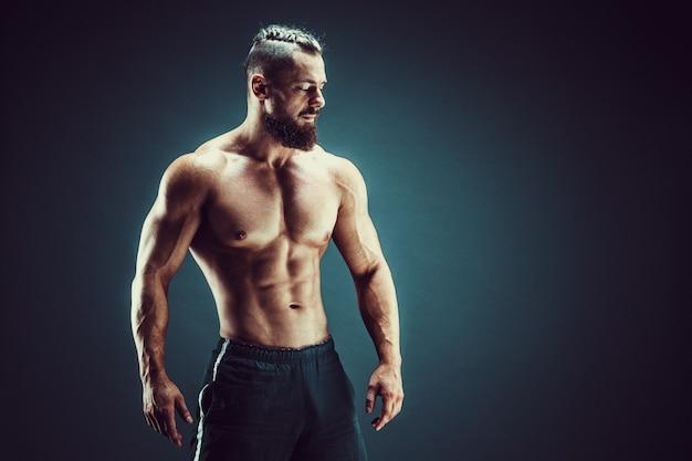 Bodybuilder posieren. mann mit muskeln der eignung auf dunklem hintergrund. Premium Fotos