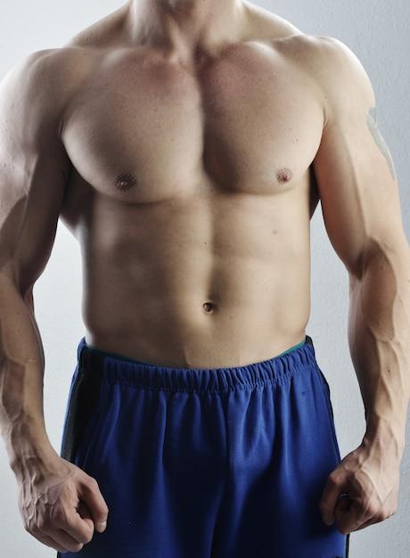 Bodybuildermeister, der im studio aufwirft Premium Fotos