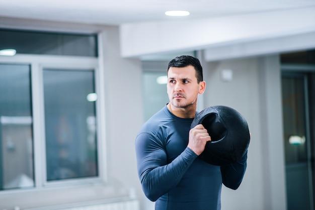 Bodybuilding-konzept. hübscher muskulöser mann, der gewichtsball hält. Premium Fotos