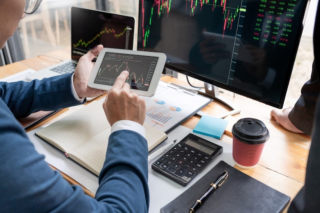 Börsenmaklerteam diskutieren mit bildschirmen analysieren von daten. Premium Fotos