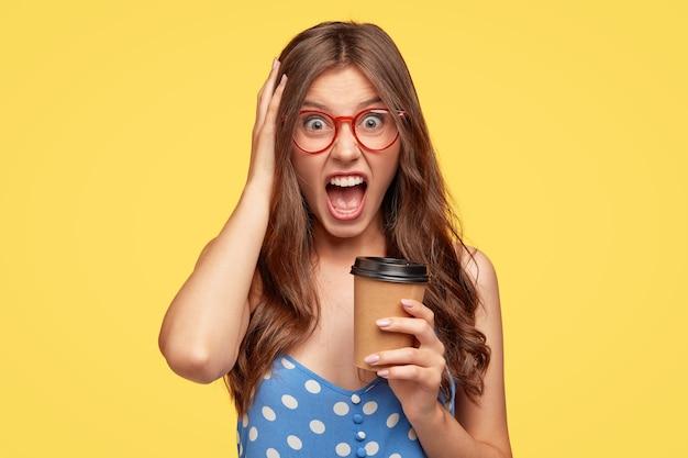 Böse junge frau mit brille, die gegen die gelbe wand aufwirft Kostenlose Fotos