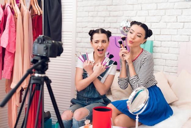 Bogger girls halten viele pinsel in die kamera. Premium Fotos