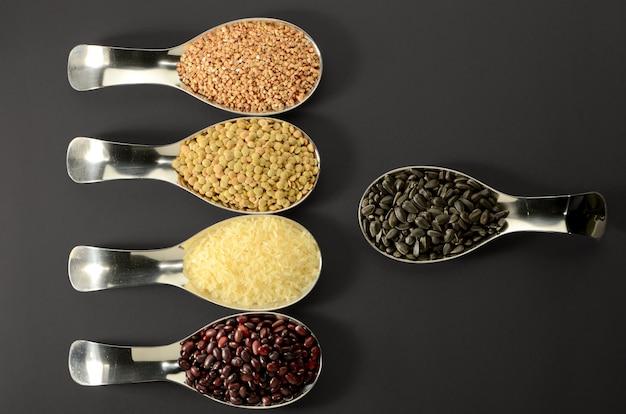 Bohnen-reis-buckwheat samen linsen im löffel auf schwarzem Premium Fotos