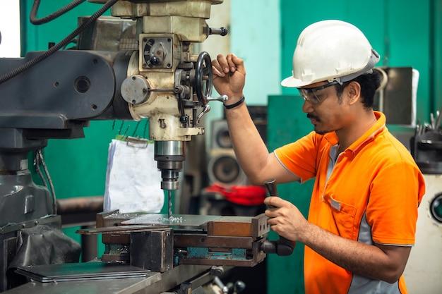 Bohrmaschine, mitarbeiter bohrmaschine in flachstahl platte mit tischbohrmaschine. Premium Fotos