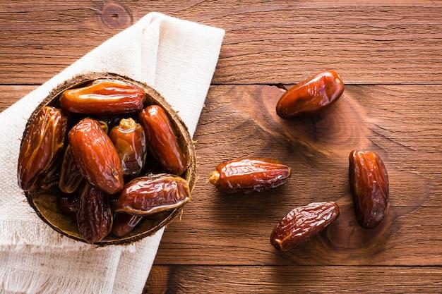 Bonbon getrocknete dattelfrüchte in einer kleinen schüssel auf serviette auf hölzerner tabelle. ansicht von oben Premium Fotos