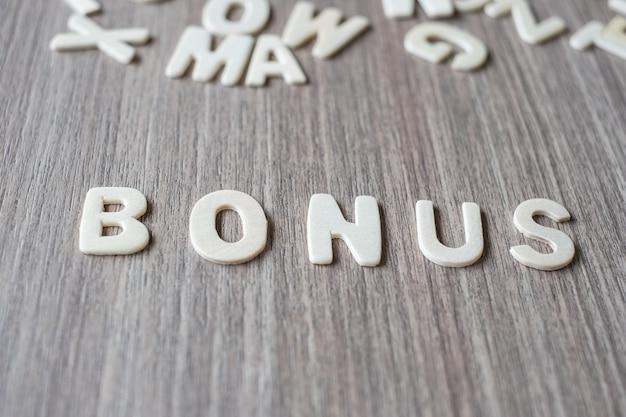 Bonus-wort von buchstaben des hölzernen alphabetes. geschäfts- und ideenkonzept Premium Fotos